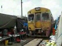 Thumbnail of Train drives through Bangkok market